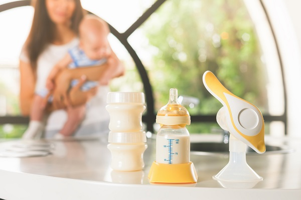 Manual breast pump, mothers breast milk is the most healthy food for newborn baby. Happy mother with infant at background at the kitchen